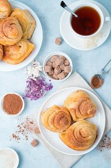 Нежный кулинарный фон со свежими булочками и чаем на голубом фоне.
