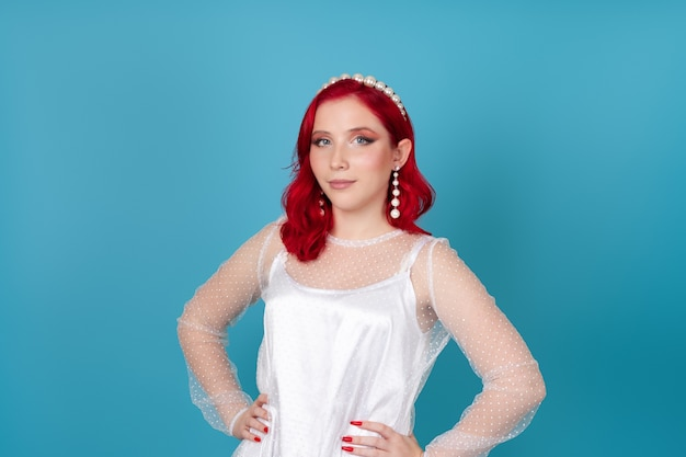 Delicate, cute woman with red hair and hands on her waist in white silk mesh dress