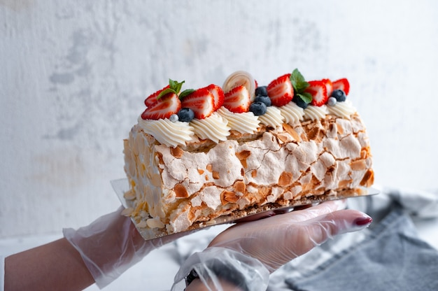 생과자 요리사의 손에 딸기와 아몬드 꽃잎이 들어간 섬세한 디저트 머랭 롤 프리미엄 사진