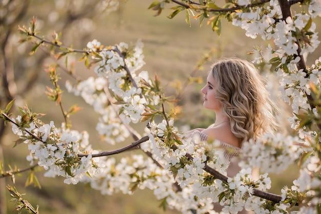 일몰에 피는 흰색 정원에 곱슬 금발 머리를 가진 섬세하고 꿈꾸는 소녀