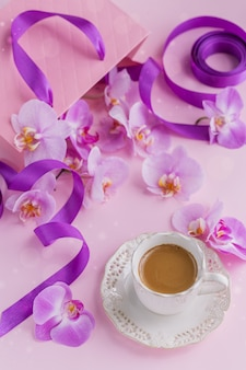 Delicate flatlay composition with morning cup of coffee with milk or cappuccino, pink gift bag and purple orchid flowers on light pink background