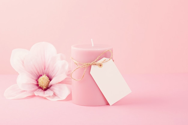 Delicate flower scented candle over the pastel pink background with copy space