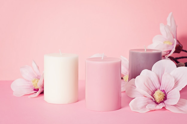 Delicate flower scented candle over pastel pink background