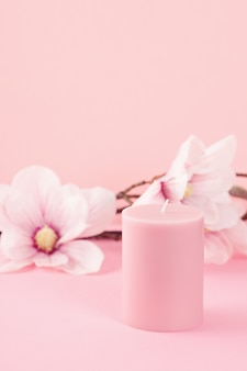 Delicate flower scented candle over pink wall