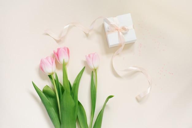繊細な新鮮なピンクのチューリップとベージュの背景にサテンのリボンが付いたギフトボックス。バレンタインデー、母の日、誕生日。グリーティングカード