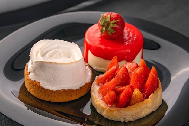 Нежные фруктовые пироги на черной тарелке. фруктовые десерты со свежей клубникой. кондитерские изделия.