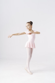 Delicate girl ballerina standing in ballet pose on white. kinds personality development concept.