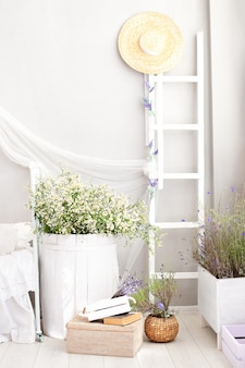 Delicate interior with a large barrel of daisies and a decorative staircase in the interior of the apartment in the style of provence. shabby chic provencal style interior in the bedroom.  rustic