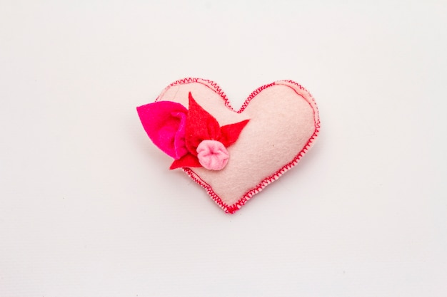 Delicate light pink felt heart isolated on white background. valentines day or wedding romantic concept