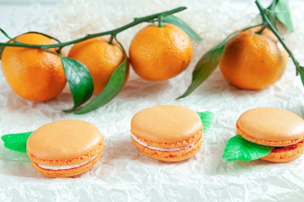 Delicate macaroons with mandarin. on white craft paper. blurred background. view from above.