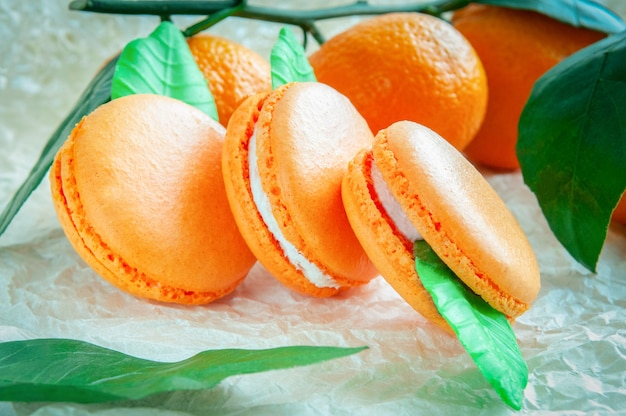Delicate macaroons with mandarin. on white craft paper. blurred background.