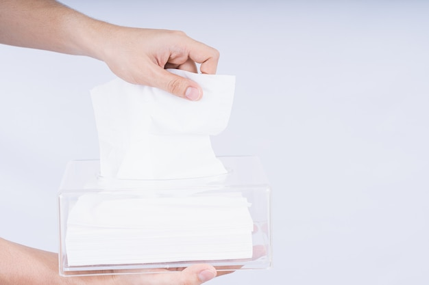 透明なクリスタルティッシュボックスから白いティッシュペーパーを引き出す繊細な男性の手