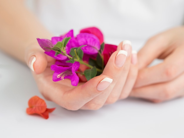 Delicate manicured hands holding flowers