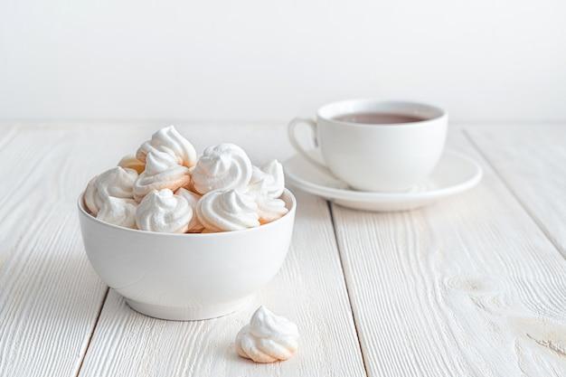 Нежные безе на белом фоне с чашкой чая. вид сбоку. кондитерские изделия.