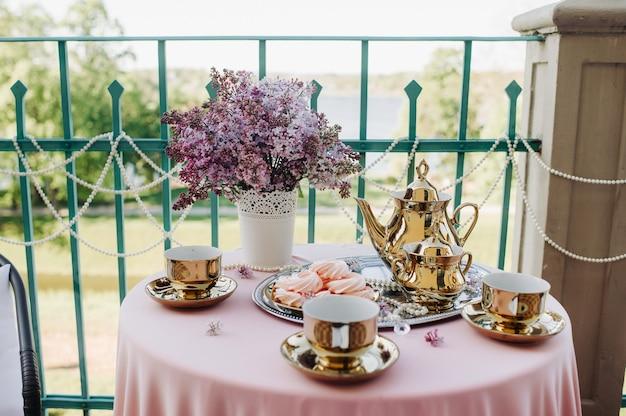 ピンクのテーブルクロスが付いたテーブルの上にライラックの花、アンティークのスプーン、皿が置かれた繊細なモーニングティーテーブルのセッティング。