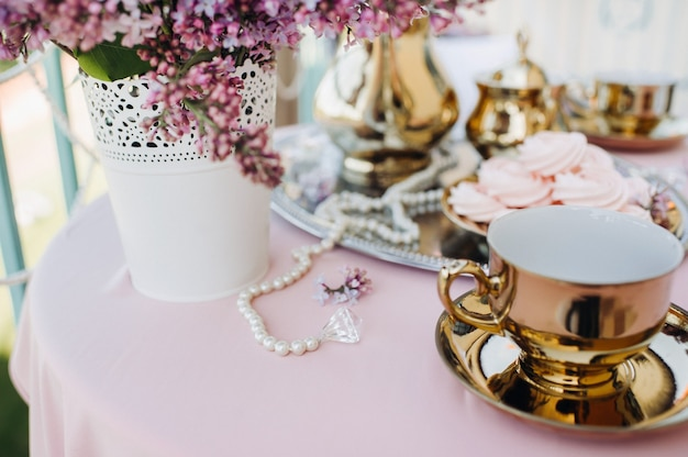 Delicate morning tea table setting with lilac flowers, antique spoons and dishes on a table with a pink tablecloth