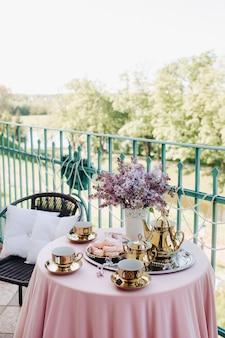 ネスヴィジ城のライラックの花、アンティークのスプーン、ピンクのテーブルクロスをかけたテーブルの皿など、繊細なモーニングティーテーブルのセッティング。