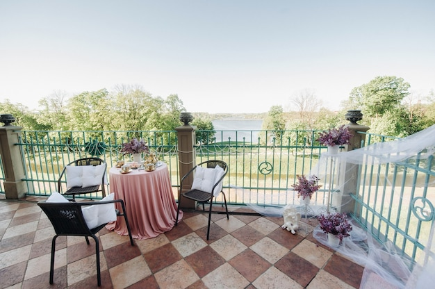 Delicate morning tea table setting with lilac flowers in nesvizh castle, antique spoons and dishes on the table with a pink tablecloth