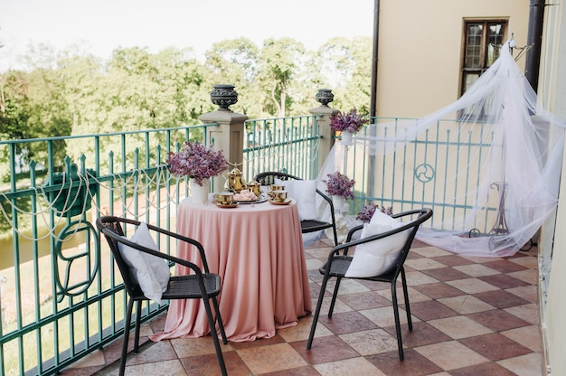 Delicate morning tea table setting with lilac flowers in nesvizh castle, antique spoons and dishes on the table with a pink tablecloth.