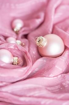 Нежные розовые елочные игрушки на фоне розовой шелковой ткани концепция праздника