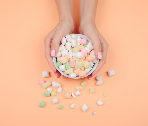 Нежный розовый маникюр на модном коралловом столе.