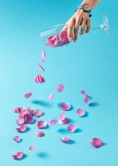 Нежные розовые лепестки роз льются из прозрачного стекла, которое девушка держит в руке с наручными часами. концепция производства вина из натуральных продуктов.
