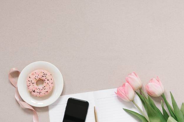 繊細なピンクのチューリップ、事務用品、ドーナツ、電話