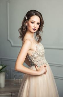 Нежный портрет молодой модельной дамы в элегантном платье пастельных тонов
