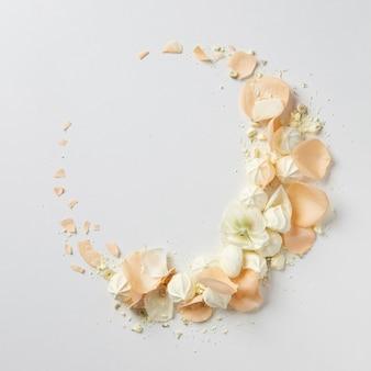 ベージュのバラとエアメレンゲが白のフラットレイに分離された繊細な丸いヴィンテージフレーム