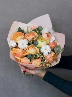 The delicate rustic floral bouquet in woman hands on grey background