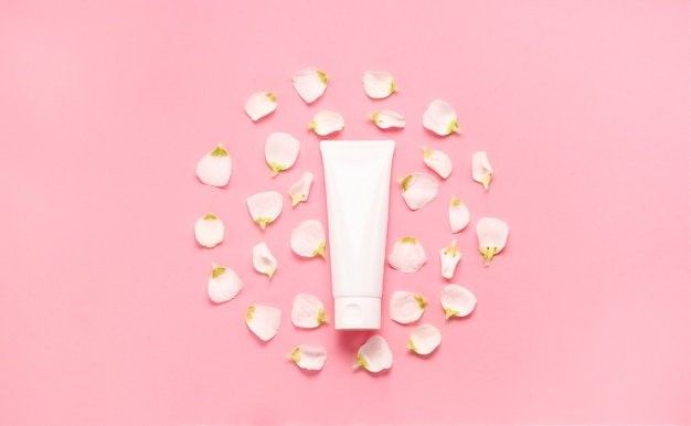 Delicate skin care cosmetic feminine flatlay. top view creative composition of face cream ,bottles and jars with cosmetic and flowers leaves on abstract background