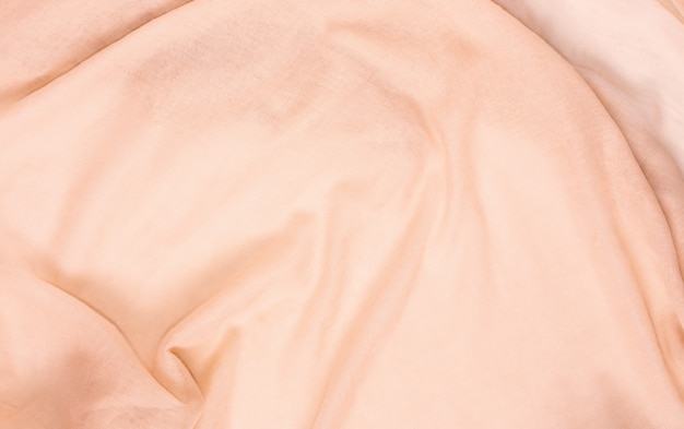 Delicate soft and wrinkled fabric cream color background texture