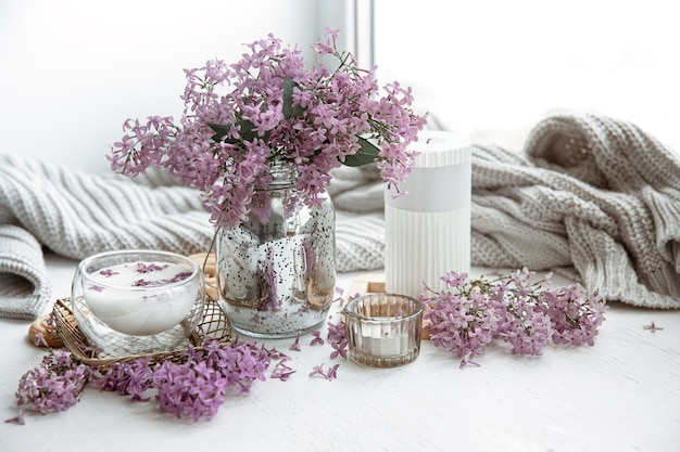 Delicate spring arrangement with flowers in a vase, a glass of milk and home decor details.