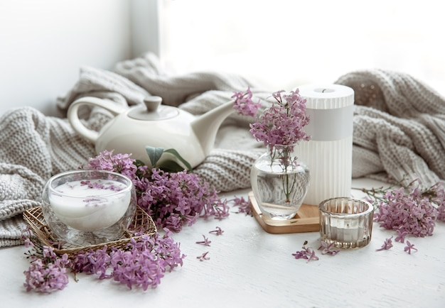 Delicate spring arrangement with flowers in a vase, a glass of milk and home decor details