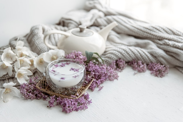Delicate spring composition with fresh flowers, a glass of milk and a knitted element