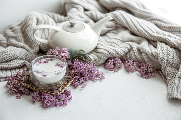 Delicate spring composition with lilac flowers, a glass of milk and a knitted element.