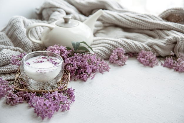 Delicate spring composition with lilac flowers, a glass of milk and a knitted element