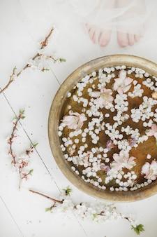 アンティークのバスタブと女性の脚の繊細な春の花