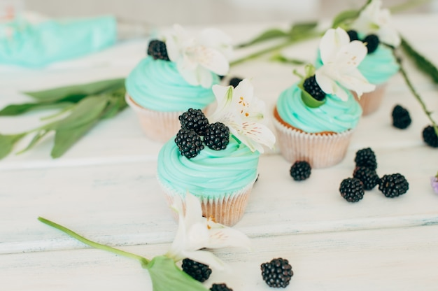 Delicate tasty muffins with mint cream decorated with fresh blac