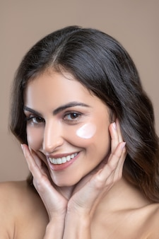 Delicate texture. close up face of smiling beautiful woman with cream on cheeks and hands near cheeks