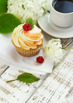 Delicate vanilla cupcakes with cream and raspberries on a white wooden surface