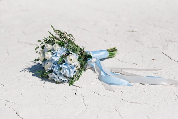 Delicate wedding bouquet of blue hydrangea, eustoma, greens with long ribbons on white cracked . wedding details in blue and white