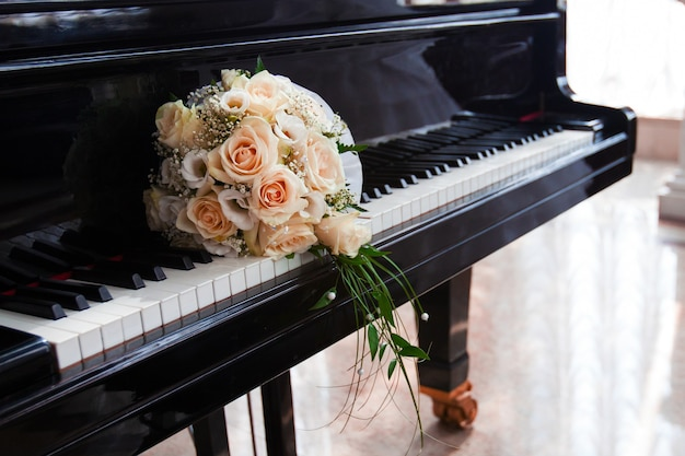 Delicate wedding bouquet of roses lies on the keys of the grand piano