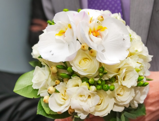 Delicate wedding bouquet of white roses, orchids and freesias in the hands of the groom close-up
