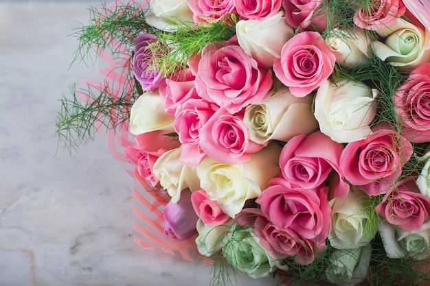 Delicate wedding bridal bouquet of beautiful white and pink roses on a white marble table