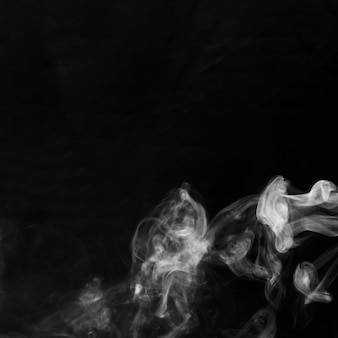 Delicate white cigarette smoke waves on black backdrop