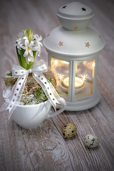Delicate white pearl hyacinth with white lantern and quail eggs on wood