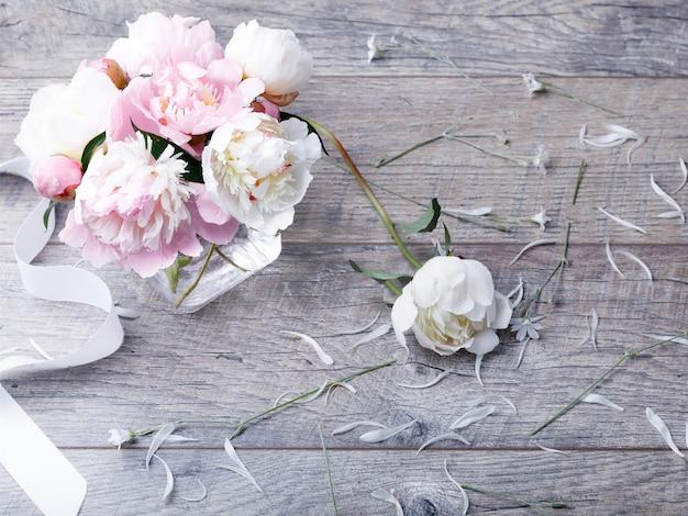 나무 판자에 꽃잎 꽃과 흰색 리본이 달린 섬세한 흰색 분홍색 모란. 오버 헤드 평면도, 평면 누워. 공간을 복사합니다. 생일, 어머니, 발렌타인, 여성, 결혼식 날 컨셉입니다.