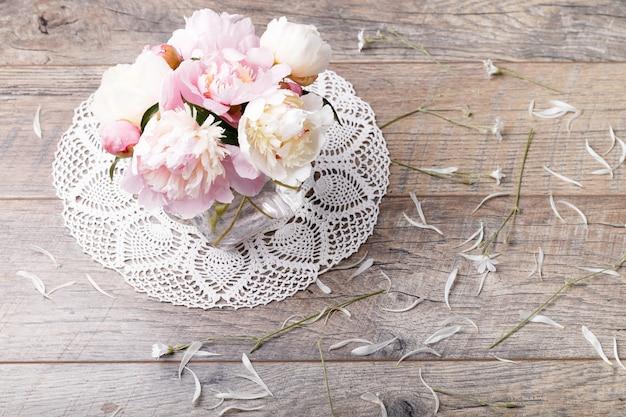 나무 판자에 꽃잎 꽃과 흰색 리본이 달린 섬세한 흰색 분홍색 모란. 오버 헤드 평면도, 평면 누워. 공간을 복사합니다. 생일, 어머니, 발렌타인, 여성, 결혼식 날 개념