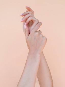 Delicate woman's hands with pink fingernails